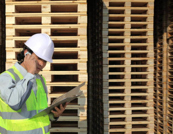 Employee in hardhat next to piles of wood pallets